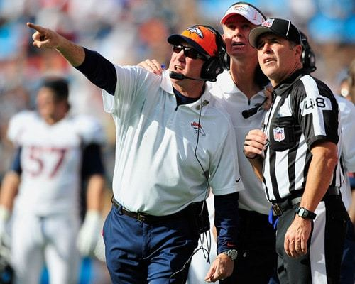 Coach John Fox of the Denver Broncos confers with NFL official head linesman, Jim Mello during a game against the Carolina Panthers. (c) Grant Halverson, Getty Images North America.